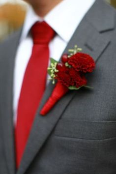 a crimson red tie and dahlia boutonniere with a dark grey suit
