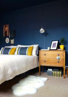 tapis pres du lit en fourrure blanc murs en bleu foncé, table d'appoint en bois clair