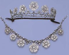 AN ANTIQUE FLORAL DIAMOND NECKLACE/TIARA  Designed as seven graduated old-cut diamond flowerheads suspended from the diamond foliate line to the knife-edge and collet backchain, with fittings for a tiara, brooches and earrings, mounted in silver and gold, circa 1880, Carrington & Co.