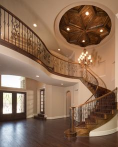 The intricate and elegant staircase, beautiful chandelier, and a detailed ceiling design make for an inviting and eye-catching entryway.
