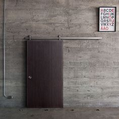The Oden sliding door hardware system in Top Mount paired with a PlybooDoor in the Noir finish. The PlybooDoor features a unique, linear pattern routed into the wood to help mitigate sound pollution.