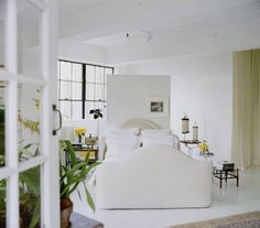 Vincente Wolf creates a partial wall backdrop so this bed can be in the middle of the room, not interfering with windows or doors, yet have a cozy feel. He is the master of white!! Floors and walls.