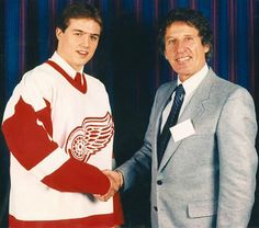 A young Steve Yzerman receives a congratulatory handshake from Mike Ilitch