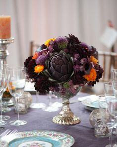 Silver vases holding teeming bunches of burgundy and purple dahlias, artichokes…