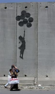A Palestinian woman and her children walk past a Banksy drawing on the controversial Israeli barrier in the West Bank city of Aram in 2005. REUTERS/Ammar Awad