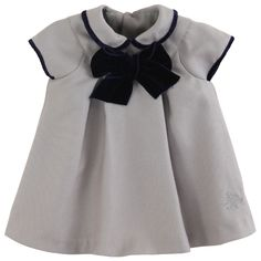 Medium grey flannel dress with a Peter Pan collar and short sleeves. Synthetic lining with Tartine & Chocolat logo print. Buttoning all the way down the back. Neckline and sleeves trimmed with a navy blue velvet braid. Large navy blue velvet bow on the chest.