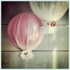 I like balloons covered in tulle and tied with a flower. Easy, cheap, and pretty.