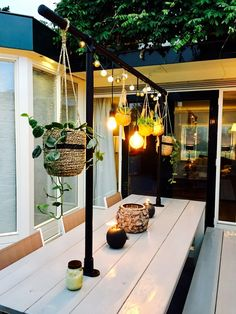 I love the idea of hanging plants and lights above an outdoor dining table to create a feature! - Home Decoration Patio Yard Ideas, Backyard Landscaping, Backyard Ideas, Patio Table, Dining Table, Garden Ideas On A Budget, Small Backyard Patio, Budget Patio, Backyard Patio Designs