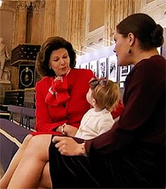 """Queen Silvia, Crown Princess Victoria and Princess Estelle of Sweden """"discussing"""" a painting of their husband/father/grandfather, King Carl XVI Gustaf."""