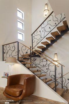 Des escaliers élégants, à la rembarde graphique et ondulée.