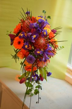 a very colourful hand shower bouquet - each flower was used individually in the bridesmaid's flowers to represent either their name, nickname or personality.