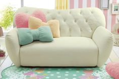 Tufted white couch with pink, yellow and blue bow pillows