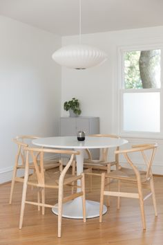 Kristen's living room transitions into the dining room easily with the open floor plan. And, the pieces are simple and timeless. The Nelson saucer pendant lamp, medium size and the Wishbone chairs in ash are both from Design Within Reach. The table is the DOCKSTA table from IKEA.