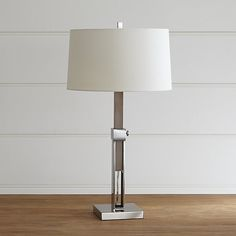 Denley Nickel Table Lamp...Linear and architectural, this lamp showcases a grey-finished wood base with brushed nickel accents, topped with a warm white cotton-linen drum shade. A turn of a knob allows the lamp's height to be easily adjusted up to 33.75 inches.  $199.