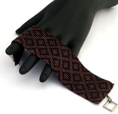 This bracelet features diamonds of matte black delica beads on a metallic dark raspberry background. The bracelet is finished off with an antique