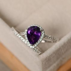 This halo ring features a 7*9mm pear cut natural amethyst and sterling silver finished with rhodium. Customization is available. It is made by hand, and it will take about 7 days to finish the ring after your payment is completed. Main stone: natural amethyst Amethyst weight: Approx 1.90 ct Metal type: sterling silver finished with rhodium Accent stone: cz  Customization is available, I also can make it with 14k solid gold (white or yellow or rose) and diamond accent stone, just feel free to…