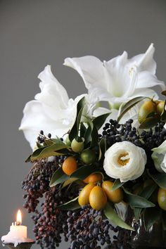 Elegant winter wedding centerpiece by Sarah Winward. Amaryllis, kumquat and privet berry.