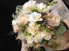 Rustic bridal bouquet of vendella roses, white freesia, Queen Anne's lace, berzillea and green hypericum berries with wheat and burlap accents.