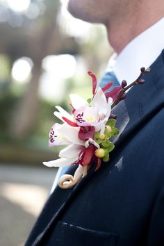 This unique boutonniere adds a pop of color to the groom's attire - photo by top South Carolina wedding photographer Leigh Webber via JunebugWeddings.com.