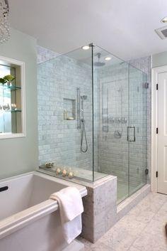 Wide wet bench / platform in modern master shower w glass panels.