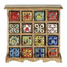 The Curios line of small drawer apothecary chests are inspired by the antique spice boxes of the far east. This brightly colored hand painted ceramic drawer design is arranged in a light brown mango w