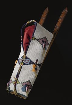 CHEYENNE BEADED HIDE BABY CARRIER    mounted on a pair of narrow pointed slats, decorated with metal tacks with a cross motif, finely and tightly sinew and thread sewn in typical colors against a white lazy-stitched glass beadwork ground, with stylized butterfly designs alternating with terraced diamond elements, trimmed with silk ribbon and beaded pendants; blue cotton cloth as lining, muslin on the back panel