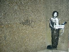 Banksy Graffiti. A stencil of Charles Manson in a prison suit, hitchhiking to anywhere, Archway, London