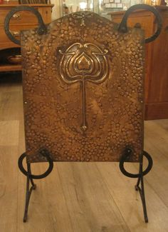 Ornate beaten copper panel with central tulip motif on wrought iron frame
