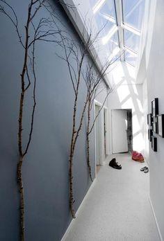 L'astuce parfaite pour les couloirs étroits: la verrière, ici sublimée par un bleu dégradé et des branches, comme une continuité du ciel