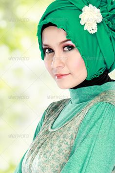 Young happy beautiful muslim woman with green costume wearing hi - Stock Photo…