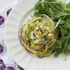 """This bright and fresh summer salad, highlighting seasonal beauties like zucchini and yellow squash, is a playful twist on your typical shaved vegetable salad. You will need a spiralizer, which is a fairly inexpensive kitchen tool that allows you to grate vegetables into long """"noodles"""" using a rotating handle, in order to achieve these whimsical veggie strands. Don't skip pressing and straining some of the liquid out of your vegetables—otherwise you'll likely find yourself with a soupy salad…"""