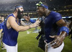 Los Angeles Dodgers' Brian Wilson, left, and Yasiel Puig, right, celebrate on the field after getting soaked in the clubhouse celebration following the Dodgers' 4-3 win over the Atlanta Braves in Game 4 of the National League baseball division series, Monday, Oct. 7, 2013, in Los Angeles. The Dodgers advanced to the NL championship series. (AP Photo/Danny Moloshok)