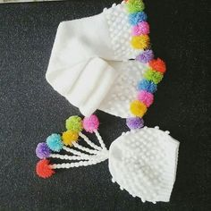 Renkli ponponlarla süslenmiş fıstıklı hoş bir model. Renkli ponponlu atkı bere takımı. 2. 3 yaş. Alıntıdır. Malzemeler : Beyaz bebe yünü 3 numara şiş 3 numara tığ