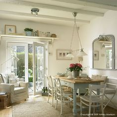 Large dining room, French doors, painted beams, large painted dining table. wooden pine. Hanging pendant lights.