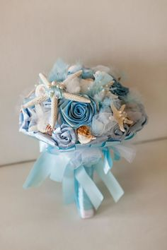 A beach-inspired bouquet filled with blue flowers, starfish and seashells. Wedding Planner: MB Wedding Design and Events.