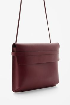 A clean design, this shoulder bag is made from structured leather with knotted adjustable straps that can be taken off and be used a clutch. Folded over and secured with a strap, it has a main cotton lined compartment and a zip pocket.