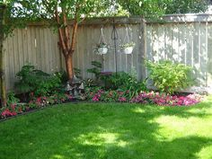 privacy fence edged with flowers and shrubs