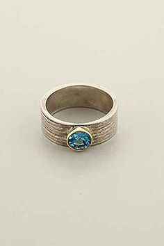 Blue Toon Ring    Hand made, two tone ring with Blue Topaz stone in gold mounting.    Band: 0.3 in. wide; stone is 0.15 in. high.  Price:$98.00
