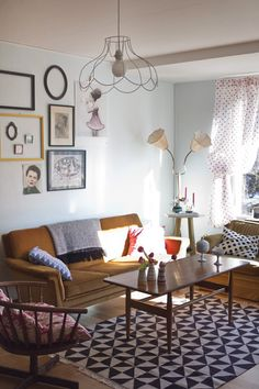Lovely.   This reminds me of my daughter Lauren.  She has a neutral sofa with pillows  . Thrift store brass lamps spray painted  with Anthropology shades.  A bold geometric rug and  a similar assortment of wall hangings.