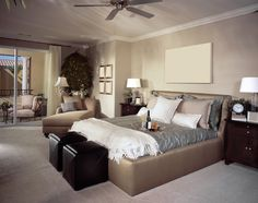 Large neutral tone designed bedroom with lounge and glass doors to private balcony