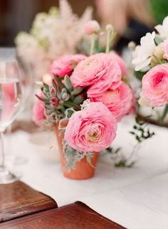pink ranunculus and succulent simple centerpiece in a clay pot