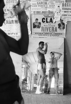 Muhammad Ali getting photographed in the mirror with a poster from his fight scene in Requiem For A Heavyweight against Mountain Rivera (Anthony Quinn).