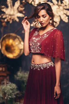 Look maroon color skirt and crop top with cape. Lehenga and cape with floral design hand embroidery thread work. They can customize the dress as per your requirement.For more detail 31 August 2018 Choli Designs, Lehenga Designs, Blouse Designs, Lehenga Crop Top, Lehenga Blouse, Cape Lehenga, Crop Top Traditional, Traditional Outfits, Indian Designer Outfits