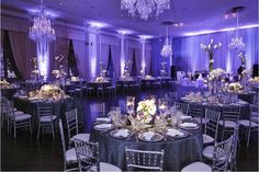 The couple's reception ballroom was awash with violet lighting. Tables were covered with grey linens and surrounded by metallic silver chairs with plush white cushions. Photo by KingenSmith