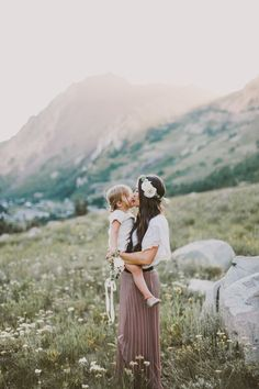 mother holding daughter in her arms and they are kissing with flower crowns