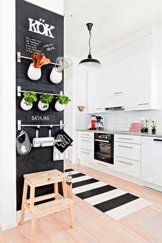 #cuisine avec plancher, meubles blancs, murs blancs, peinture ardoise avec tringles pour rangement mural