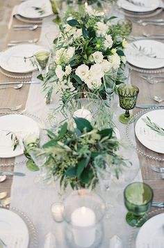 A pastel colored table runner beautifully compliments a long wooden banquet table. #WeddingCenterpieces