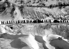 """A column of American Marines marches down a canyon road dubbed """"Nightmare Alley"""" during their retreat from Chosin Reservoir, Korea, 1950."""