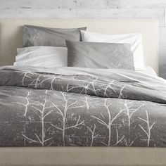 branch out.  Painterly trees take root in a modern forest by Chicago-based designer Noël Ashby where white branches grow graphic on grey.  Soft 200-thread-count cotton duvet cover has nonslip corner ties and hidden button closure; reverses to white.  Dreamy with coordinating crumpled trees shams. Designed exclusively for CB2 by Noël Ashby100% cotton200 thread countDuvet cover has nonslip corner ties and hidden button closure; reverses to whiteMachine wash; do not dry clean.