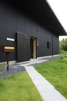 芝生の前庭に敷かれたコンクリートブロックのアプローチ。<br /> 大き目の板戸が玄関戸。 専門家:向井一規が手掛けた、芝生を通るアプローチ(『HDFの家』〜雑木林と語らう家〜)の詳細ページ。新築戸建、リフォーム、リノベーションの事例多数、SUVACO(スバコ)